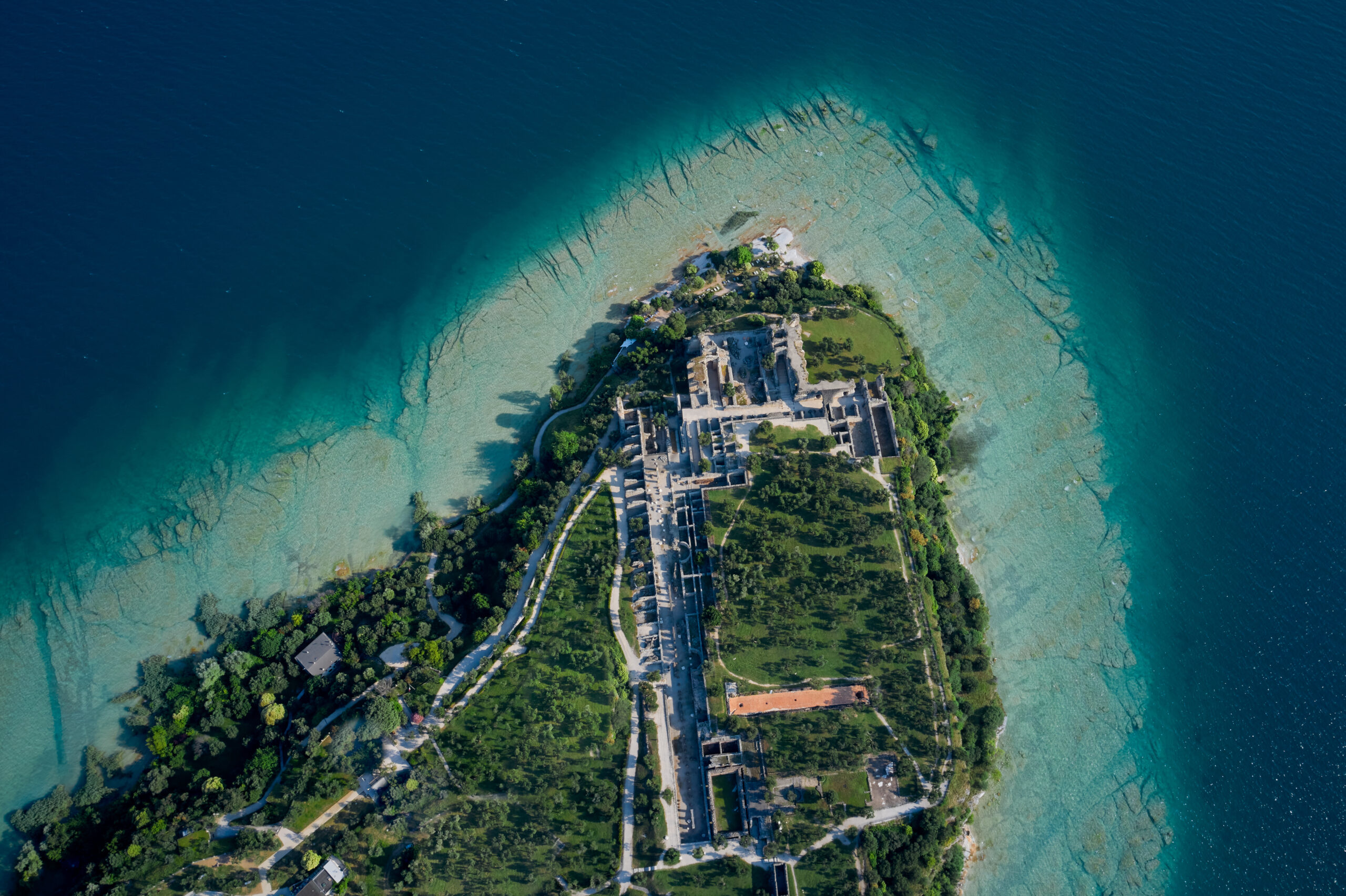 The view of cryptoporticus roman ruins Grotte di Catullo. Archaeological site of Grotte di Catullo, Sirmione, Italy early morning aerial view. lake garda.